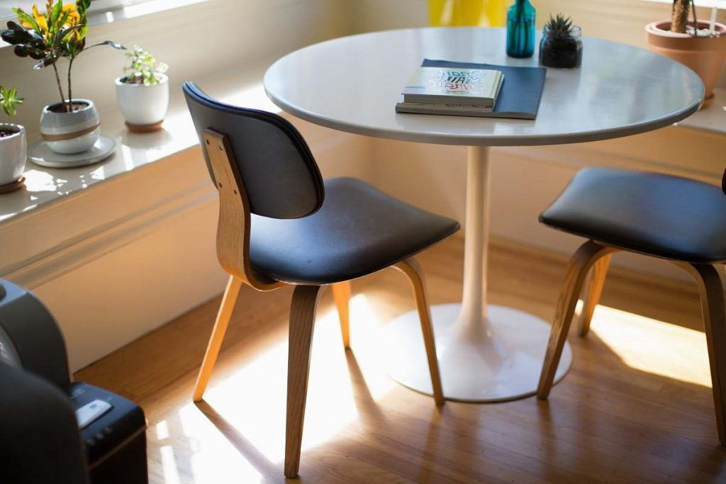 furniture-round-white-dining-table-beside-two-chairs-on-brown-hardwood-flooring-table-table-image.jpg